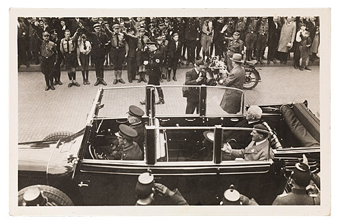 Black-and-white photo in horizontal format showing an open-top car with Hindenburg, Hitler and uniformed attendants. In the background there are people in both civilian and military dress, their arms raised in the Hitler salute. Two photographers are standing to the right of the car.
