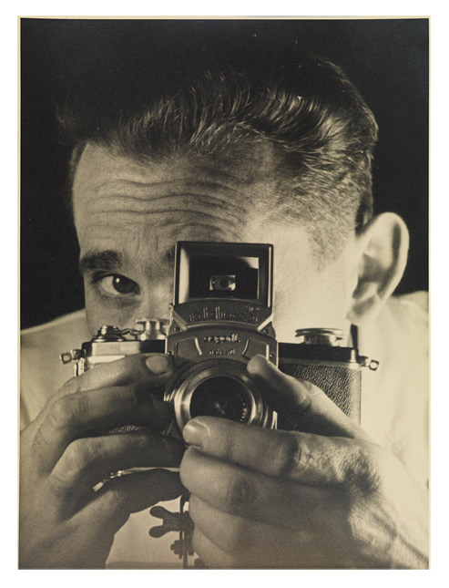 Photograph showing a man with his face concealed behind a camera that he holds in both hands; one of his eyes is visible through the viewfinder.