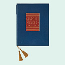 A book bound in blue and red leather with a gold embossed cover and a gold-colored tassel.