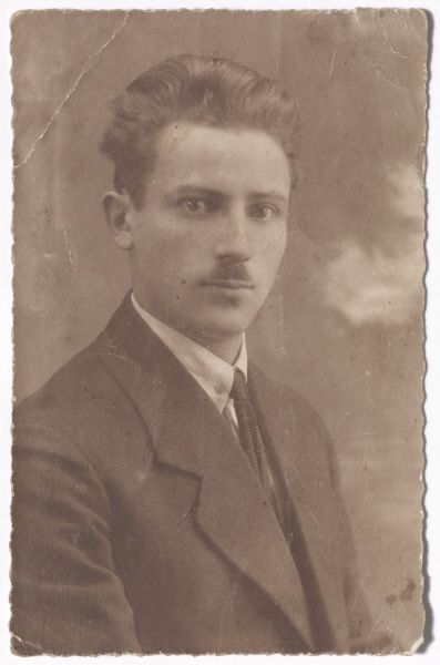 Black-and-white portrait photo of a young man with a moustache in a suit