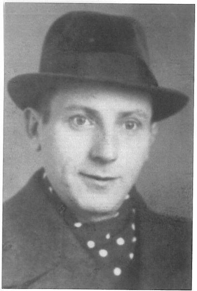 Black-and-white portrait of a man with a hat and a polka dot cravat