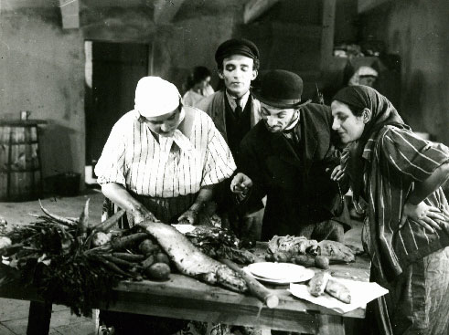 Film still of several people standing around a market stall looking at a fish