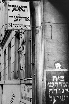 Entrance of the building at no. 31 with a view of the facade and Hebrew signs (partial view)