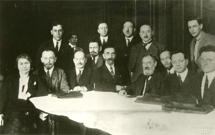 Group of men with briefcases  at a desk