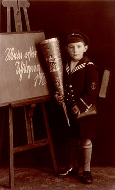 Boy in a sailor's suit with a school bag in front of a chalkboard reading �My first day of school 193...�
