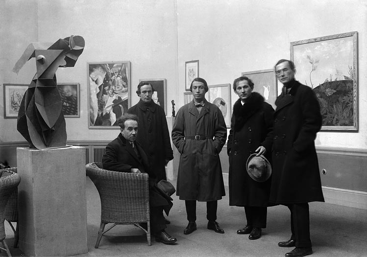 Five men in coats in an exhibition room, with a painting in the background and a sculpture to the left