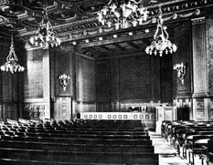 Historical view of the interior showing the stage with seats and chandeliers