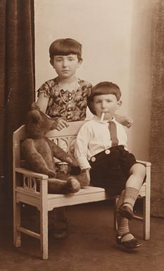 Girl and boy with a teddy bear on a small bench