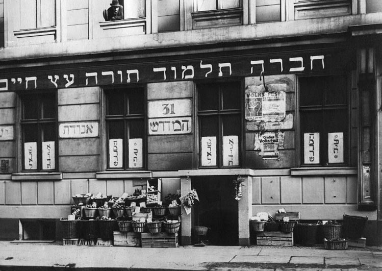Black-and-white photo of a building facade with Hebrew signs and baskets in front of the door