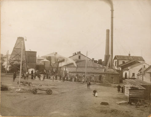 Historical photo of the oil refinery, people, buildings, and vehicles