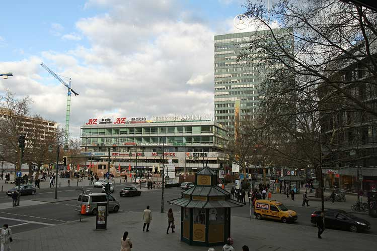 View of the square with people, cars, and buildings