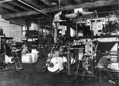 View of a room with rotary printing presses; one worker is standing on a ladder and others can be seen in the background