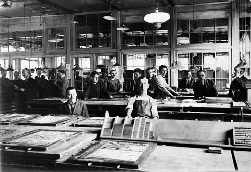Men in front of tables with typecases