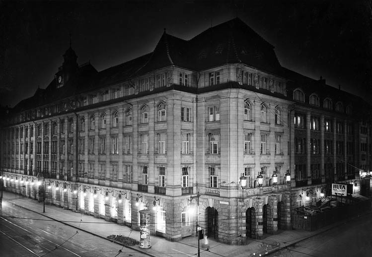 Black-and-white photo of an illuminated corner building.