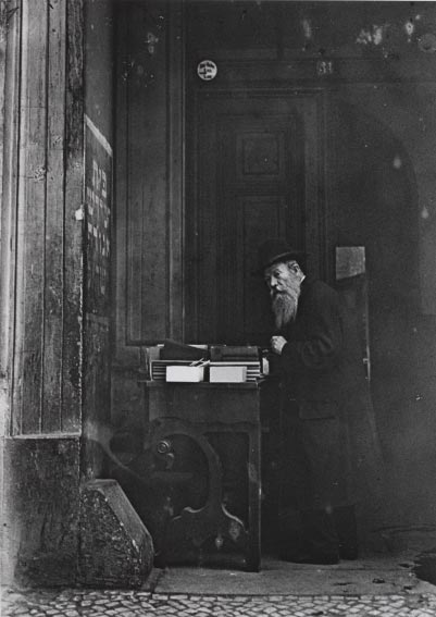 Black-and-white photo of an elderly man with a table of books in the building�s entrance