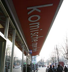 Sign for the Komische Oper seen from below, with passers-by and street view