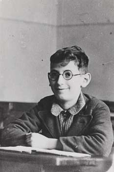 Boy with glasses sitting at a desk in school