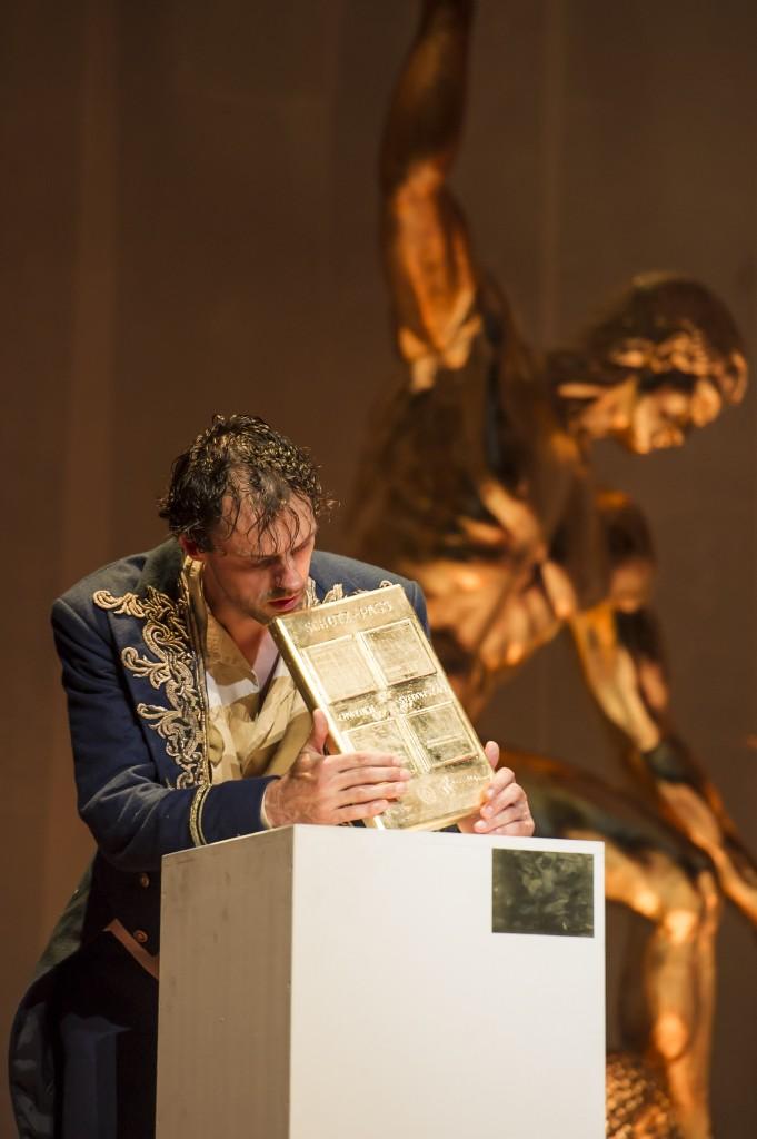 Man in front of golden statue
