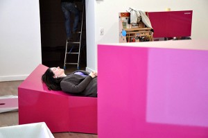 The curator Michal Friedlander lying on a showcase