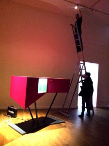 A showcase in magenta and people on a ladder
