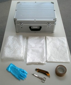 A case, bubble wrap, thick plastic wrap, tissue paper, gloves, scissors and cutter, tape