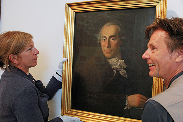 A woman and a man holding a painting against the wall