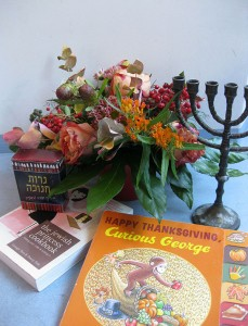 "A menora, flowers, and the book ""Curious George"""