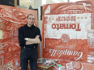 A man in front of big paintings in red