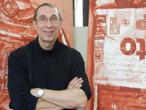 A smiling man in front of red paintings