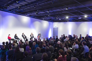 Five panelists on the stage in front of a big audience