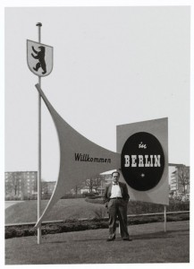 "Fred Stein, behind him signs saying ""Welcome to Berlin"" (in German)"