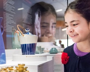 A girl looking at a showcase with ceramic objects