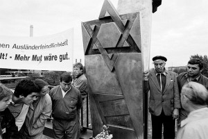"Demonstrators in front of a memorial with the Magen David and a poster with the words ""Ausländerfeindlichkeit"" (xenophobia) and ""We need more courage."""