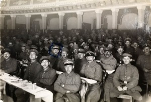 Men in uniform occupy seats in a theater auditorium.