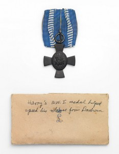 "An Order of Merit in form of a cross and an envelope with the note ""Harry's WWI medal helped speed his release from Dachau"""