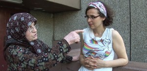 An elderly woman talks to a young woman