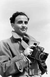 Black and white picture of an man with a camera in his hands. He looks directly at the phtographer