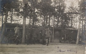 black and white photograph of several uniformed soldiers in front of a cabin in the woods