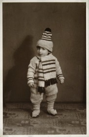 Black and white photo of an infant wearing hat and scarf.