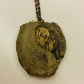 Golden pendant with the depiction of a women's head