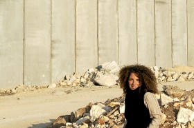 Photo of the artist standing in front of the wall
