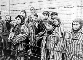 Black-white photograph of surviving children of the concentration camp in Auschwitz standing behind a fence