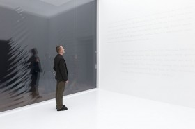 Man in a completly white room with white letters on the wall