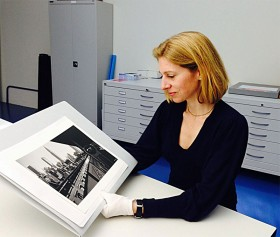 color photograph of a woman holding the photograph of Ilse Bing