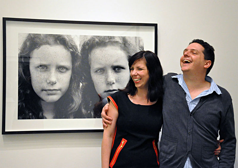 color photograph of a young couple smiling and standing in a gallery