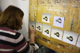 A woman is painting coins