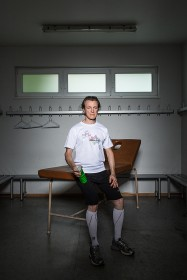 Portrait of a man in sports wear with a bottle in a locker room