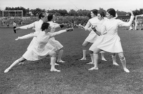 Black-and-white photo: six women fencers at a sporting event