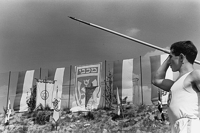 Black and white photo: javelin thrower at athletic grounds
