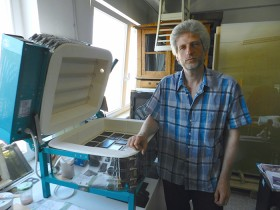 A man stands next to an electric kiln